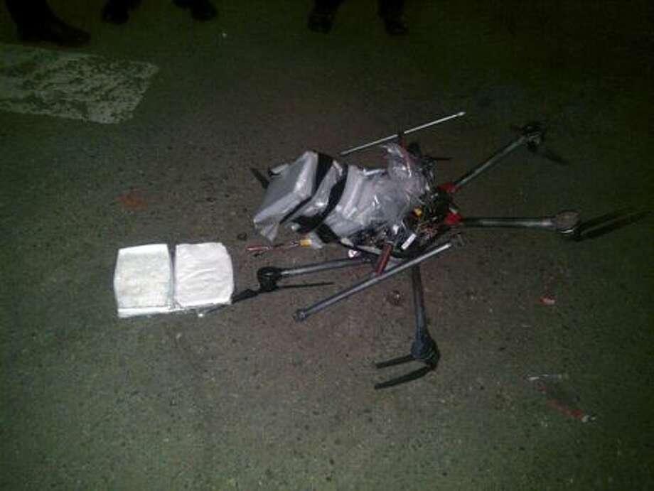 .En esta imagen divulgada por la policía municipal de Tijuana el 21 de enero de 2015 se ve un drone (avión no tripulado) cargado con paquetes de metanfetamina en el suelo, después de haberse estrellado contra el estacionamiento de un supermercado en Tijuana el 20 de enero de 2015. Según la policía, seis paquetes de la droga, con un peso de más de seis libras, fueron adheridos a la nave operada por control remoto. Las autoridades están investigando dónde se originó el vuelo y quién lo estaba controlando. La policía dijo que no es la primera vez que han visto que narcotraficantes usan drones para contrabandear drogas a través de la frontera. Otros métodos innovadores incluyen catapultas, aviones ligeros y túneles. Photo: Secretaría De Seguridad Pública De Tijuana/AP