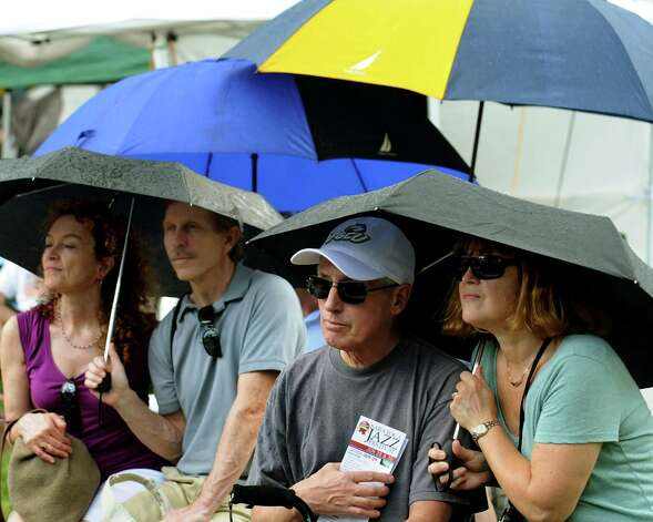 Couples huddle under umbrellas as they listen to music at the Gazebo Stage during the 33rd annual Freihofer's Jazz Festival on Saturday, June 29, 2013, at Saratoga Performing Arts Center in Saratoga Springs, N.Y. (Cindy Schultz / Times Union) Photo: Cindy Schultz / 00022973A