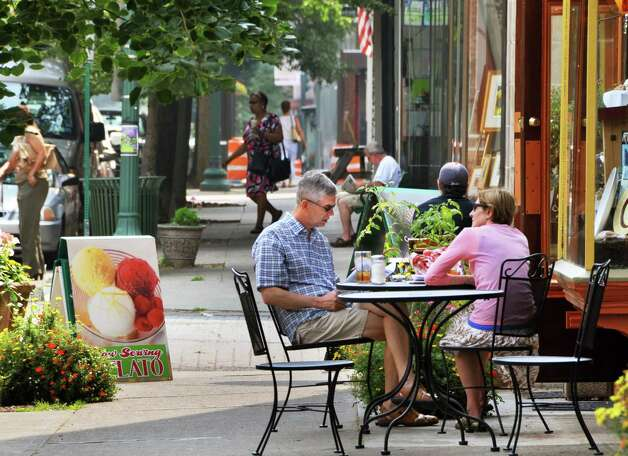 Australian tourists motoring through the state, Stefan and Kerry Trofimovs enjoy a sidewalk table at the Illium Cafe in downtown Troy Thursday morning July 23, 2009. The couple stopped in Troy to take in the historic architecture and stained glass windows.  (John Carl D'Annibale / Times Union) Photo: John Carl D'Annibale / 00004818A