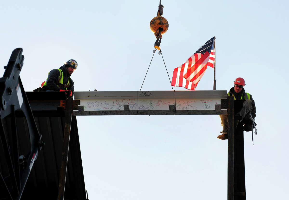 The final steel beam for the new $75 million, 372,000 square foot Jewish Senior Services is put into place by steel workers Joe Plourde, left, and Paul Moore III, at the site on Park Avenue in Bridgeport, Conn. on Thursday Jan. 24, 2015.