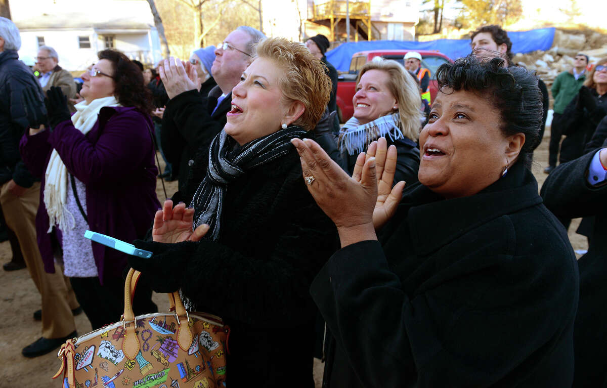 Jewish Senior Center employee Soncerria Holland, at right, and Bridgeport City Councilwoman Michelle Lyons, center, applaud as the final steel beam for the new $75 million, 372,000 square foot Jewish Senior Services building is put into place by steel workers at the new site on Park Avenue in Bridgeport, Conn. on Thursday Jan. 24, 2015.