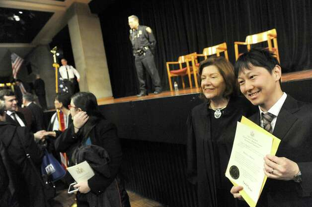 Lawyer Yukihiro Takemoto from Japan gets his photograph taken with Presiding Justice of the Third Department Karen K. Peters following a swearing-in ceremony for newly admitted members of the New York State Bar at the Empire State Plaza Convention Center on Thursday Jan. 22, 2015 in Albany, N.Y. (Michael P. Farrell/Times Union) Photo: Michael P. Farrell / 00030281A