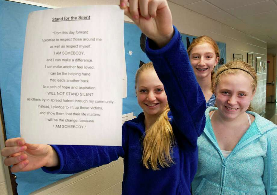 Madison Thibodeau, 13, holds the Stand for the Silent pledge as she poses for a photo with Grace Hansen, center, and Kelly Wargo, right, at Scofield Magnet Middle School on Thursday, January 22, 2015. The girls brought the anti-bullying campaign to their school. Photo: Lindsay Perry / Stamford Advocate