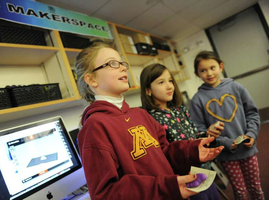 "Second graders Ellie Englund, left, Filippa Keszti, center, and Lucy Carpenter talk in the ""maker space"" of the new ""learning commons"" of the International School at Dundee in Old Greenwich, Conn. Thursday, Jan. 22, 2015.  The school transformed its library media center into a much more interactive space where students spend more time doing hands-on activities.  There is a new ""maker space"" where students create CAD designs to print with a 3D printer, different teaching spaces often incorporating outside programs and STEM activities all while keeping the elements of a traditional library media center. Photo: Tyler Sizemore / Greenwich Time"