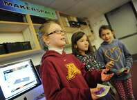 """Second graders Ellie Englund, left, Filippa Keszti, center, and Lucy Carpenter talk in the """"maker space"""" of the new """"learning commons"""" of the International School at Dundee in Old Greenwich, Conn. Thursday, Jan. 22, 2015.  The school transformed its library media center into a much more interactive space where students spend more time doing hands-on activities.  There is a new """"maker space"""" where students create CAD designs to print with a 3D printer, different teaching spaces often incorporating outside programs and STEM activities all while keeping the elements of a traditional library media center."""