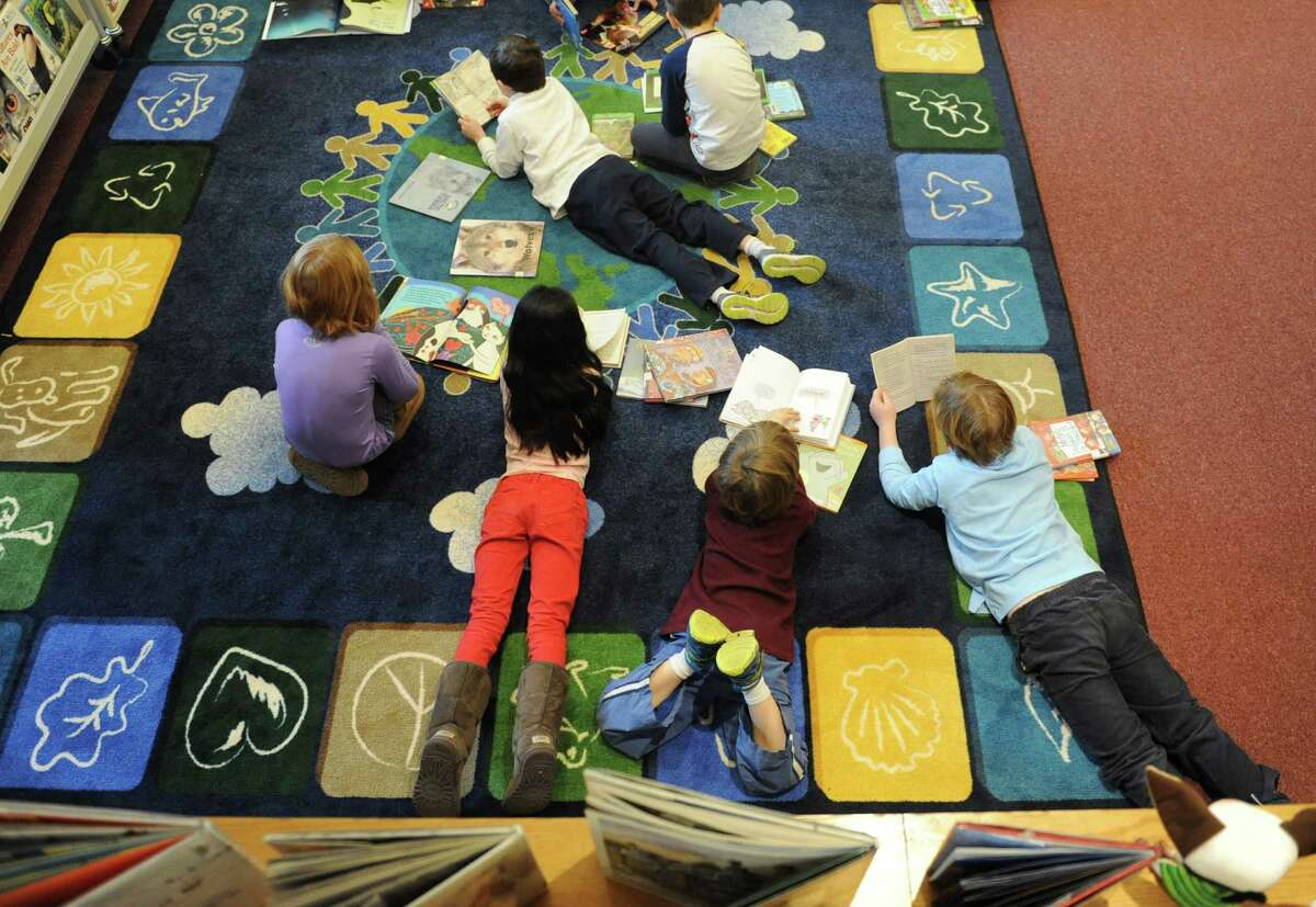 Children spread out on the floor to read books in the new