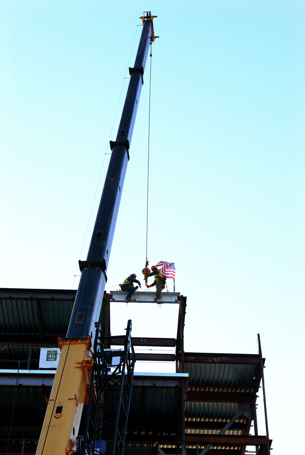 The final steel beam for the new $75 million, 372,000 square foot Jewish Senior Services is put into place by steel workers Joe Plourde, left, and Paul Moore III, at the new site on Park Avenue in Bridgeport, Conn. on Thursday Jan. 24, 2015.