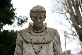 A stature of Father Junipero Serra done in the 1930s watches over the cemetery at the Mission Dolores.