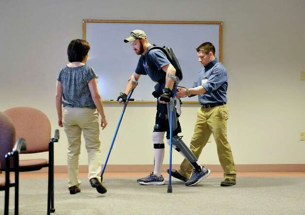 Patient Justin Neff from Madison uses the ReWalk exoskeleton suit to walk during an event at Sunnyview Rehabilitation Hospital on Thursday, Jan. 22, 2015, in Schenectady, N.Y.  The ReWalk exoskeleton suit uses a technology with motorized legs that power the knee and hip movements to help paraplegics and others with lower limb disabilities to walk again.  A computer based system uses motion sensors to control the leg movements in response to subtle changes in the upper body movements and shifts in balance.  Crutches are used for stability and a backpack worn by the patient holds the computer system and the battery that provides power to the suit.  Neff sustained his injury in October 2014 when he fell off a roof while working on it.  Neff arrived at Sunnyview in November.  Also pictured are Barb Scheidel, left, neuro-vascular physical therapy team leader at Sunnyview, and Cono Cirone, a physical therapist at Sunnyview.   (Paul Buckowski / Times Union) Photo: Paul Buckowski / 00030262A