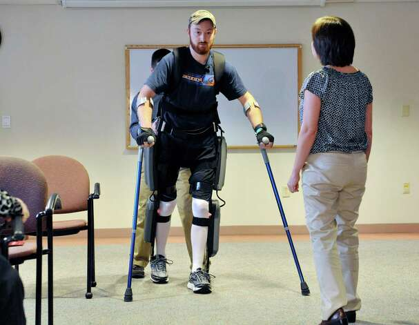 Patient Justin Neff from Madison uses the ReWalk exoskeleton suit to walk during an event at Sunnyview Rehabilitation Hospital on Thursday, Jan. 22, 2015, in Schenectady, N.Y.  The ReWalk exoskeleton suit uses a technology with motorized legs that power the knee and hip movements to help paraplegics and others with lower limb disabilities to walk again.  A computer based system uses motion sensors to control the leg movements in response to subtle changes in the upper body movements and shifts in balance.  Crutches are used for stability and a backpack worn by the patient holds the computer system and the battery that provides power to the suit.  Neff sustained his injury in October 2014 when he fell off a roof while working on it.  Neff arrived at Sunnyview in November.  Also pictured are Barb Scheidel, foreground, neuro-vascular physical therapy team leader at Sunnyview, and Cono Cirone, background, a physical therapist at Sunnyview.   (Paul Buckowski / Times Union) Photo: Paul Buckowski / 00030262A