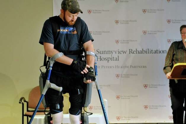Patient Justin Neff from Madison uses a keypad on his wrist to set the mode on the ReWalk exoskeleton suit  during an event at Sunnyview Rehabilitation Hospital on Thursday, Jan. 22, 2015, in Schenectady, N.Y.  The ReWalk exoskeleton suit uses a technology with motorized legs that power the knee and hip movements to help paraplegics and others with lower limb disabilities to walk again.  A computer based system uses motion sensors to control the leg movements in response to subtle changes in the upper body movements and shifts in balance.  Crutches are used for stability and a backpack worn by the patient holds the computer system and the battery that provides power to the suit.  Neff sustained his injury in October 2014 when he fell off a roof while working on it.  Neff arrived at Sunnyview in November.     (Paul Buckowski / Times Union) Photo: Paul Buckowski / 00030262A