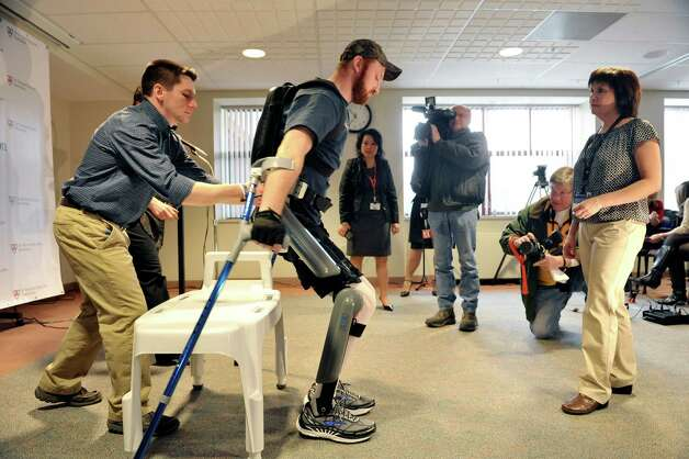 Patient Justin Neff from Madison rises up as he wears the ReWalk exoskeleton suit during an event at Sunnyview Rehabilitation Hospital on Thursday, Jan. 22, 2015, in Schenectady, N.Y.  The ReWalk exoskeleton suit uses a technology with motorized legs that power the knee and hip movements to help paraplegics and others with lower limb disabilities to walk again.  A computer based system uses motion sensors to control the leg movements in response to subtle changes in the upper body movements and shifts in balance.  Crutches are used for stability and a backpack worn by the patient holds the computer system and the battery that provides power to the suit.  Neff sustained his injury in October 2014 when he fell off a roof while working on it.  Neff arrived at Sunnyview in November.  Also pictured are Cono Cirone, left, a physical therapist at Sunnyview and  Barb Scheidel, right, neuro-vascular physical therapy team leader at Sunnyview.  (Paul Buckowski / Times Union) Photo: Paul Buckowski / 00030262A