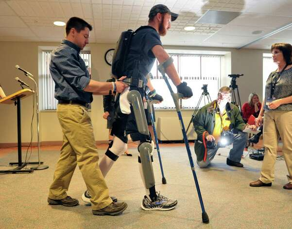 Patient Justin Neff from Madison walks as he wears the ReWalk exoskeleton suit during an event at Sunnyview Rehabilitation Hospital on Thursday, Jan. 22, 2015, in Schenectady, N.Y.  The ReWalk exoskeleton suit uses a technology with motorized legs that power the knee and hip movements to help paraplegics and others with lower limb disabilities to walk again.  A computer based system uses motion sensors to control the leg movements in response to subtle changes in the upper body movements and shifts in balance.  Crutches are used for stability and a backpack worn by the patient holds the computer system and the battery that provides power to the suit.  Neff sustained his injury in October 2014 when he fell off a roof while working on it.  Neff arrived at Sunnyview in November.  Also pictured are Cono Cirone, left, a physical therapist at Sunnyview and  Barb Scheidel, right, neuro-vascular physical therapy team leader at Sunnyview.  (Paul Buckowski / Times Union) Photo: Paul Buckowski / 00030262A