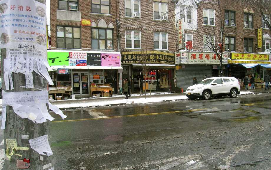 This Jan. 9, 2015 photo shows a lamppost with storefronts and homemade signs in Chinese on a commercial strip in the Sunset Park section in the Brooklyn borough of New York. The Chinatown located in Lower Manhattan is New York City's most famous Asian enclave but a section of Sunset Park has become one of the city's biggest Chinese neighborhoods in recent years. (AP Photo/Beth J. Harpaz)  ORG XMIT: MER2015011513435957 Photo: Beth J. Harpaz / AP
