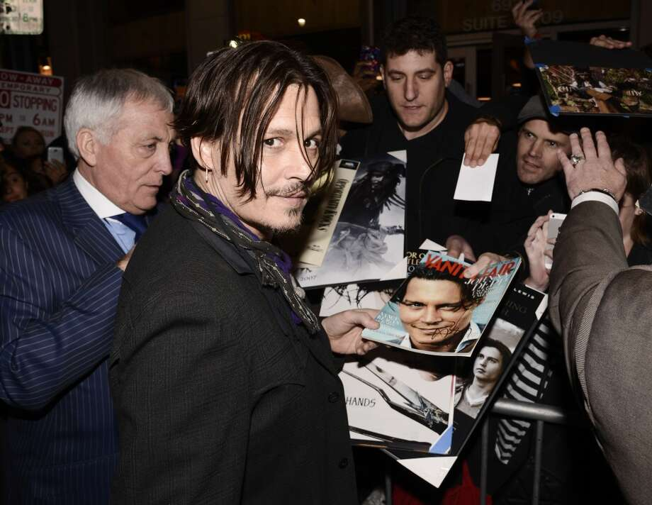 """Actor Johnny Depp signs memorabilia for fans at the premiere of the feature film """"Mortdecai"""" in Los Angeles on Wednesday, Jan. 21, 2015. Photo: Dan Steinberg, Associated Press"""