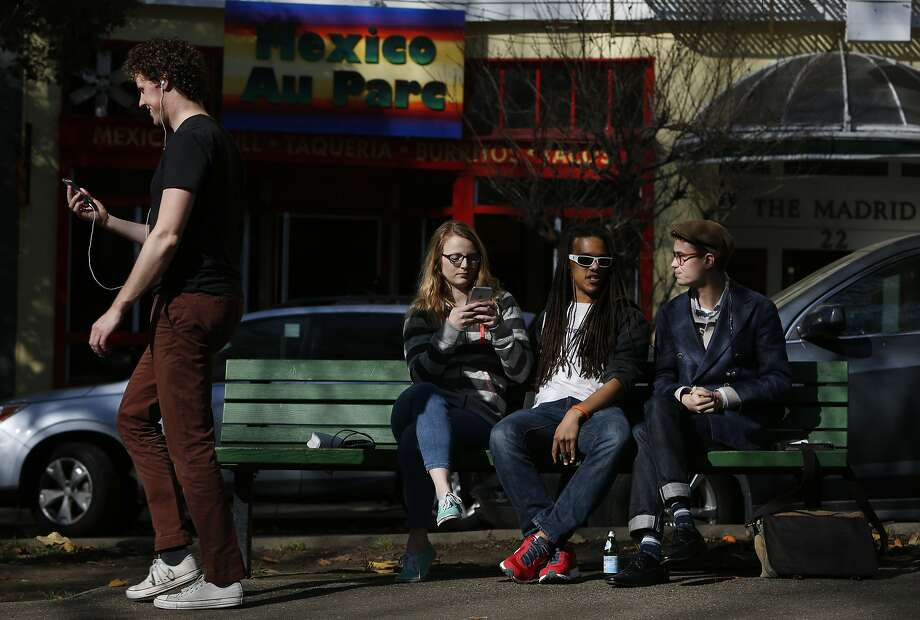 Natalie Gilbert, 25, left, Zach Fogg, 23, both of a wearable technology company hang out with Jackson Fall, 18, a freelance graphic designer in South Park Jan. 22, 2015 in San Francisco, Calif. Photo: Leah Millis, The Chronicle