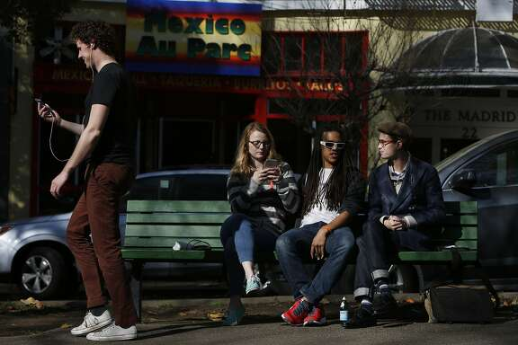 Natalie Gilbert, 25, left, Zach Fogg, 23, both of a wearable technology company hang out with Jackson Fall, 18, a freelance graphic designer in South Park Jan. 22, 2015 in San Francisco, Calif.