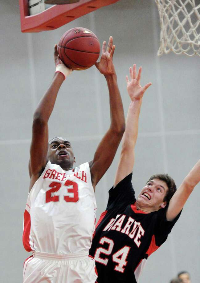 At left, Leonel Hyatt (#23) of Greenwich scores on a layup over Dylan Reilly (#24) of Fairfield Warde during the boys high school basketball game between Greenwich High School and Fairfield Warde High School at Greenwich, Conn., Thursday night, Jan. 22, 2015. Photo: Bob Luckey / Greenwich Time