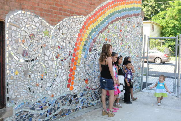 Students get their photo taken in front of a giant mosaic mural made by students outside the Ark Community Charter School after the annual Moving Up Ceremony  Friday, June 27, 2014 in Troy, N.Y. (Lori Van Buren / Times Union archive) Photo: Lori Van Buren / 00027545A
