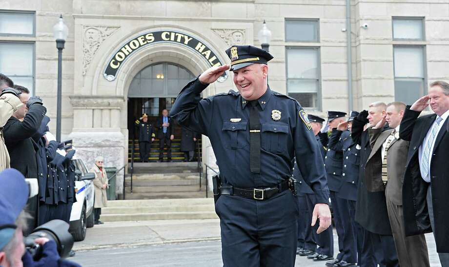 Assistant Police Chief Jim Ward salutes members of the Cohoes Police Department, the Cohoes Fire Department, friends and family who formed an honor corridor for him to walk through outside Cohoes City Hall on Thursday, Jan. 22, 2015 in Cohoes, N.Y.  Ward is retiring after 32 years with the police department. (Lori Van Buren / Times Union) Photo: Lori Van Buren / 00030298A
