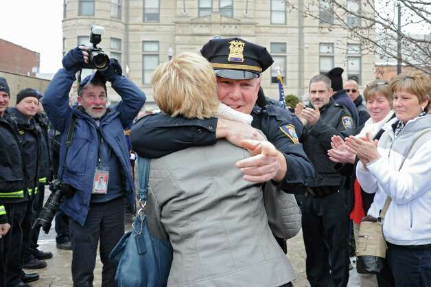 Assistant Police Chief Jim Ward gets a hug from his wife Marie as members of the Cohoes Police Department, the Cohoes Fire Department, friends and family formed an honor corridor for him to walk through outside Cohoes City Hall on Thursday, Jan. 22, 2015 in Cohoes, N.Y.  Ward is retiring after 32 years with the police department. (Lori Van Buren / Times Union) Photo: Lori Van Buren / 00030298A