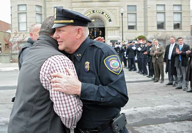 Jerry Oliver of Cohoes, left, hugs his friend Assistant Police Chief Jim Ward as members of the Cohoes Police Department, the Cohoes Fire Department, friends and family formed an honor corridor for Ward to walk through outside Cohoes City Hall on Thursday, Jan. 22, 2015 in Cohoes, N.Y.  Ward is retiring after 32 years with the police department. (Lori Van Buren / Times Union) Photo: Lori Van Buren / 00030298A