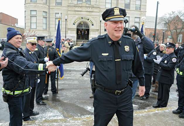 Assistant Police Chief Jim Ward salutes and shakes hands of members of the Cohoes Police Department, the Cohoes Fire Department, friends and family who formed an honor corridor for him to walk through outside Cohoes City Hall on Thursday, Jan. 22, 2015 in Cohoes, N.Y.  Ward is retiring after 32 years with the police department. (Lori Van Buren / Times Union) Photo: Lori Van Buren / 00030298A