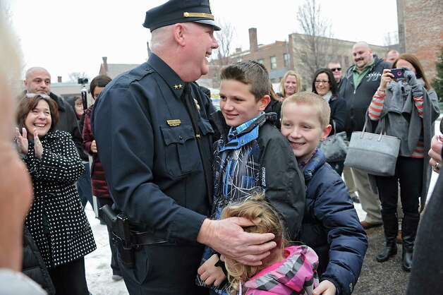 Assistant Police Chief Jim Ward gets a hug from his grandchildren Jordan, 11, Noah, 9, and Brooke, 3, after members of the Cohoes Police Department, the Cohoes Fire Department, friends and family formed an honor corridor for him to walk through outside Cohoes City Hall on Thursday, Jan. 22, 2015 in Cohoes, N.Y.  Ward is retiring after 32 years with the police department. (Lori Van Buren / Times Union) Photo: Lori Van Buren / 00030298A