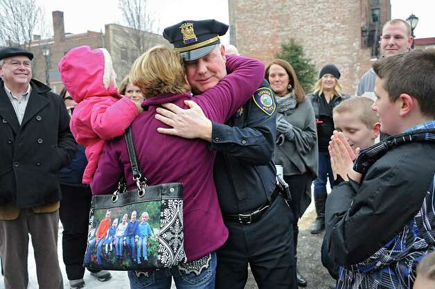 Assistant Police Chief Jim Ward gets a hug from his sister-in-law Diane Ward of Halfmoon and Diane's granddaughter Adelynn, 2, after members of the Cohoes Police Department, the Cohoes Fire Department, friends and family formed an honor corridor for him to walk through outside Cohoes City Hall on Thursday, Jan. 22, 2015 in Cohoes, N.Y.  Ward is retiring after 32 years with the police department. (Lori Van Buren / Times Union) Photo: Lori Van Buren / 00030298A