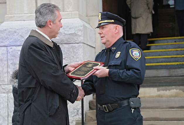 William Cox, Undersheriff with the Albany County Sheriff's Office, left, presents a plaque of appreciation to Assistant Police Chief Jim Ward outside Cohoes City Hall on Thursday, Jan. 22, 2015 in Cohoes, N.Y. Ward is retiring after 32 years with the police department. (Lori Van Buren / Times Union) Photo: Lori Van Buren / 00030298A