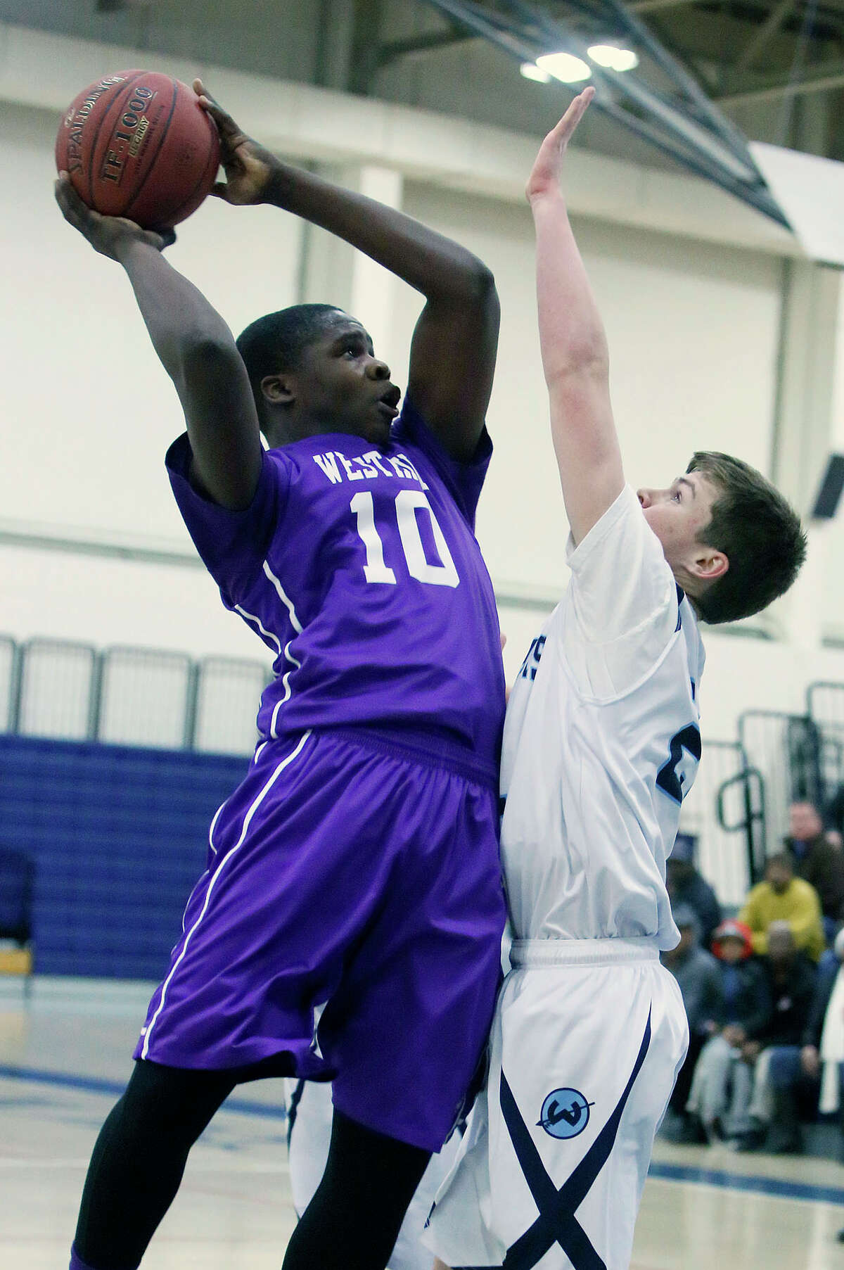 Westhill's Tyrell Alexander puts up a shot while under pressure from Wilton 's Jack Williams during their basketball game at Wilton High School in Wilton, Conn., on Thursday, Jan. 22, 2015. Westhill won, 72-67.