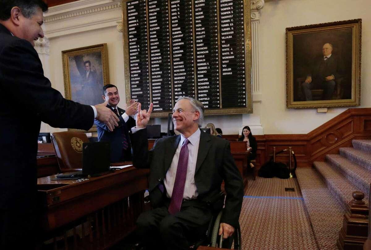 Texas Gov.-elect Greg Abbott, right, flashes the
