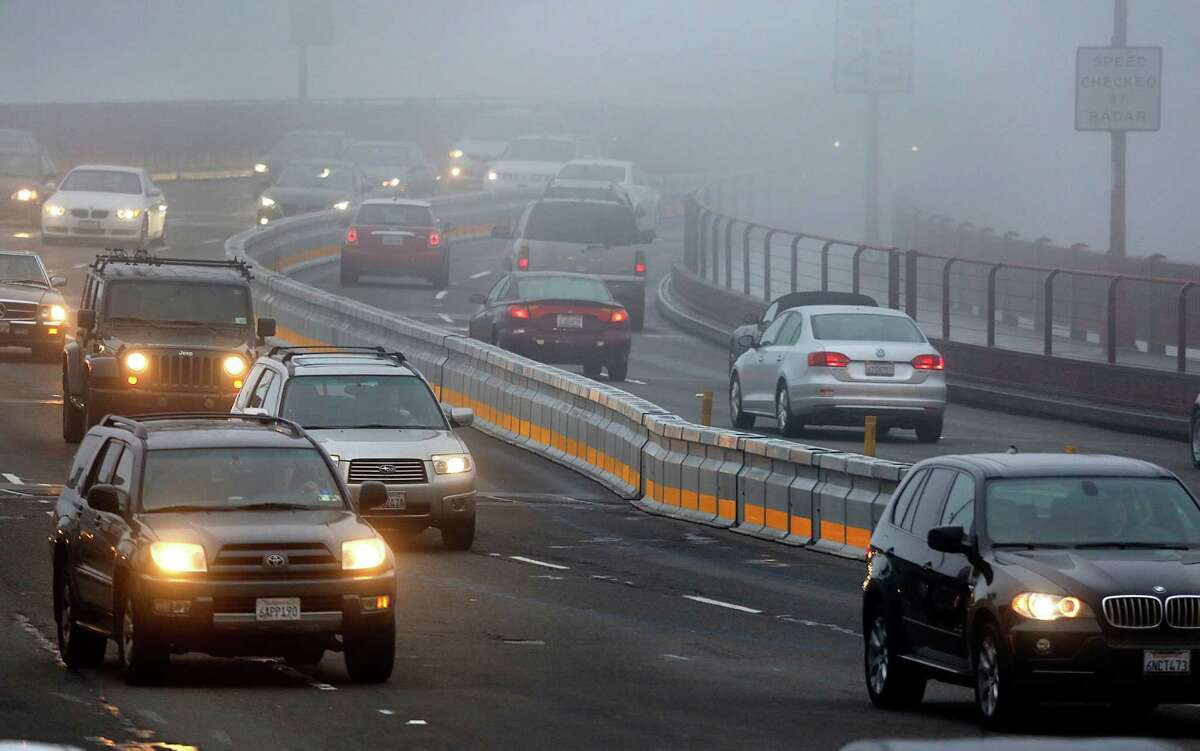 Morning traffic passes by the new Golden Gate Bridge barrier this month.