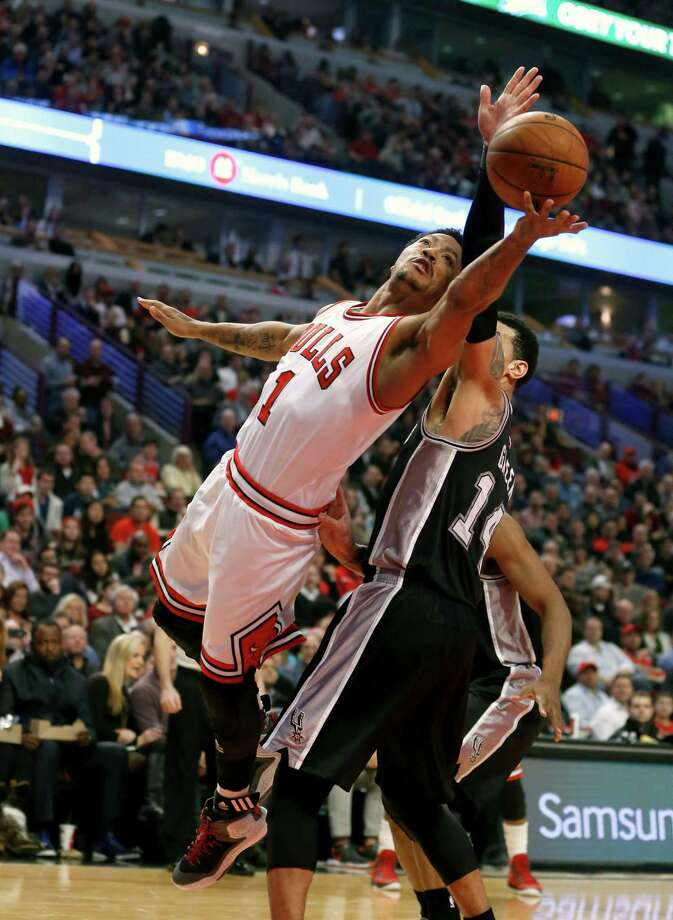 Chicago Bulls guard Derrick Rose (1) shoots past San Antonio Spurs guard Danny Green (14) during the first half of an NBA basketball game Thursday, Jan. 22, 2015, in Chicago. (AP Photo/Charles Rex Arbogast) ORG XMIT: CXA101 Photo: Charles Rex Arbogast / AP