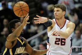 Atlanta Hawks guard Kyle Korver (26) passes as Indiana Pacers forward Luis Scola, of Argentina, defends during the first half of an NBA basketball game, Wednesday, Jan. 21, 2015, in Atlanta. (AP Photo/John Amis)