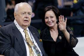New Orleans Saints owner Tom Benson sits on the sideline with his wife, Gayle Benson, before an NFL football game against the Green Bay Packers on Oct. 26 in New Orleans.