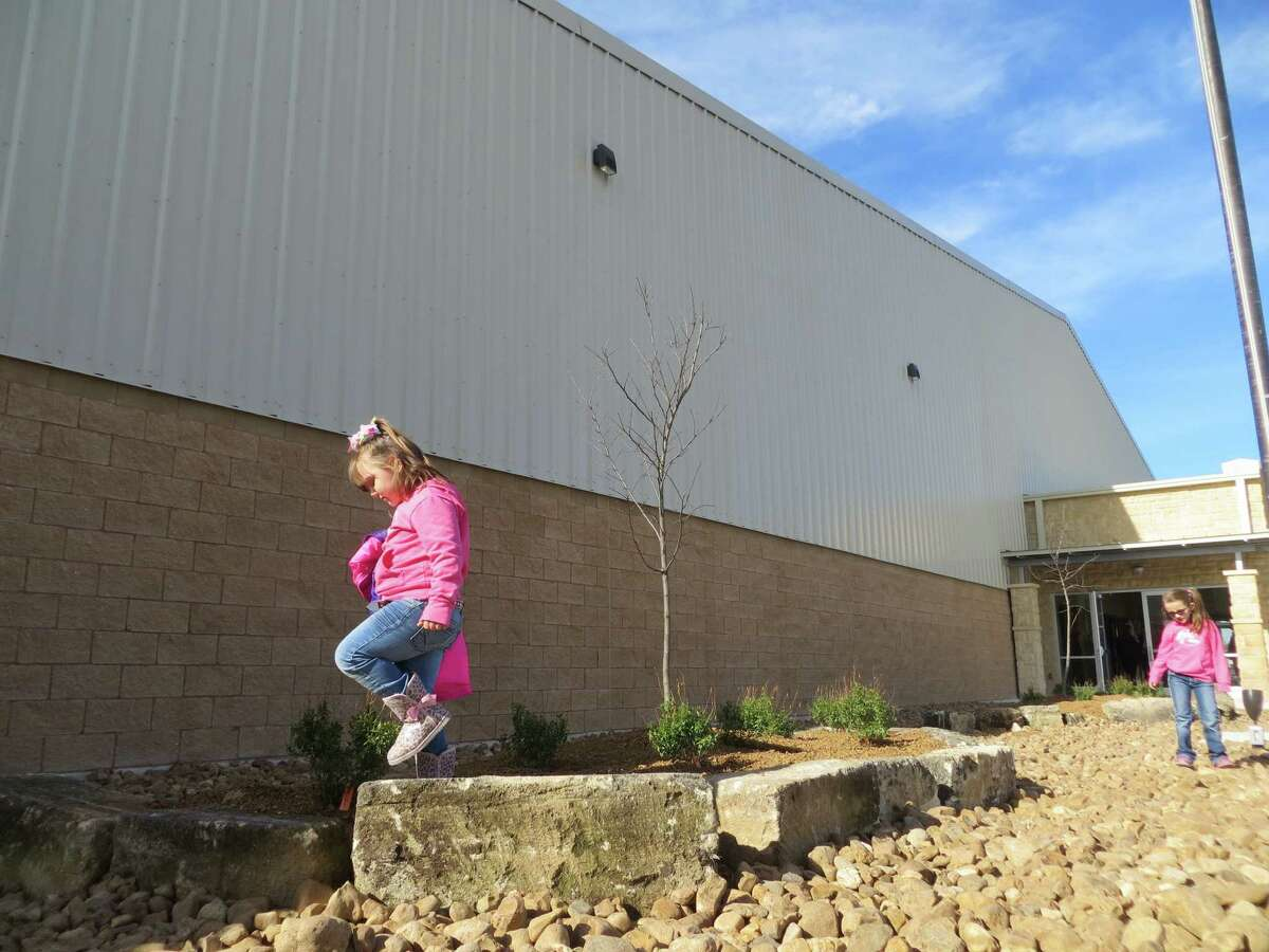 Cali Craddock (foreground) and Catarina Craddock play on the rocks outside the new $3.7 million event hall built by Kerr County at the Hill Country Youth Exhibit Center in Kerrville.