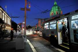 Passengers board a MUNI under a streetlight that is out on the darkened corner of Van Ness and Grove St., near City Hall in San Francisco, CA, on Tuesday, December 30, 2014.