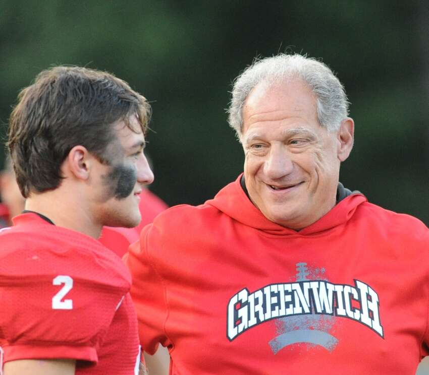 Greenwich High School head football coach Rich Albonizio, right, speaks with his player, Peter Agro, left, prior to the game between Darien High School and Greenwich High School at Greenwich, Friday night, Sept. 19, 2014. Darien defeated Greenwich, 33-26.