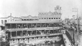 The building in the foreground was home to the San Antonio Express between 1890-1895. The building was on the San Antonio River front at Losoya. In the background, behind the Express building is the Dullnig Building (tower) and the Schulz Palm Garden (center).