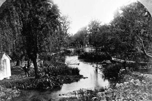 San Pedro Springs in 1869. Named by the Spanish in 1708, San Pedro Springs became the city of San Antonio's first park in 1852. J.J. Durler, whose house was located at the head of the springs, was responsible for building many of the park's early bridges and walkways.
