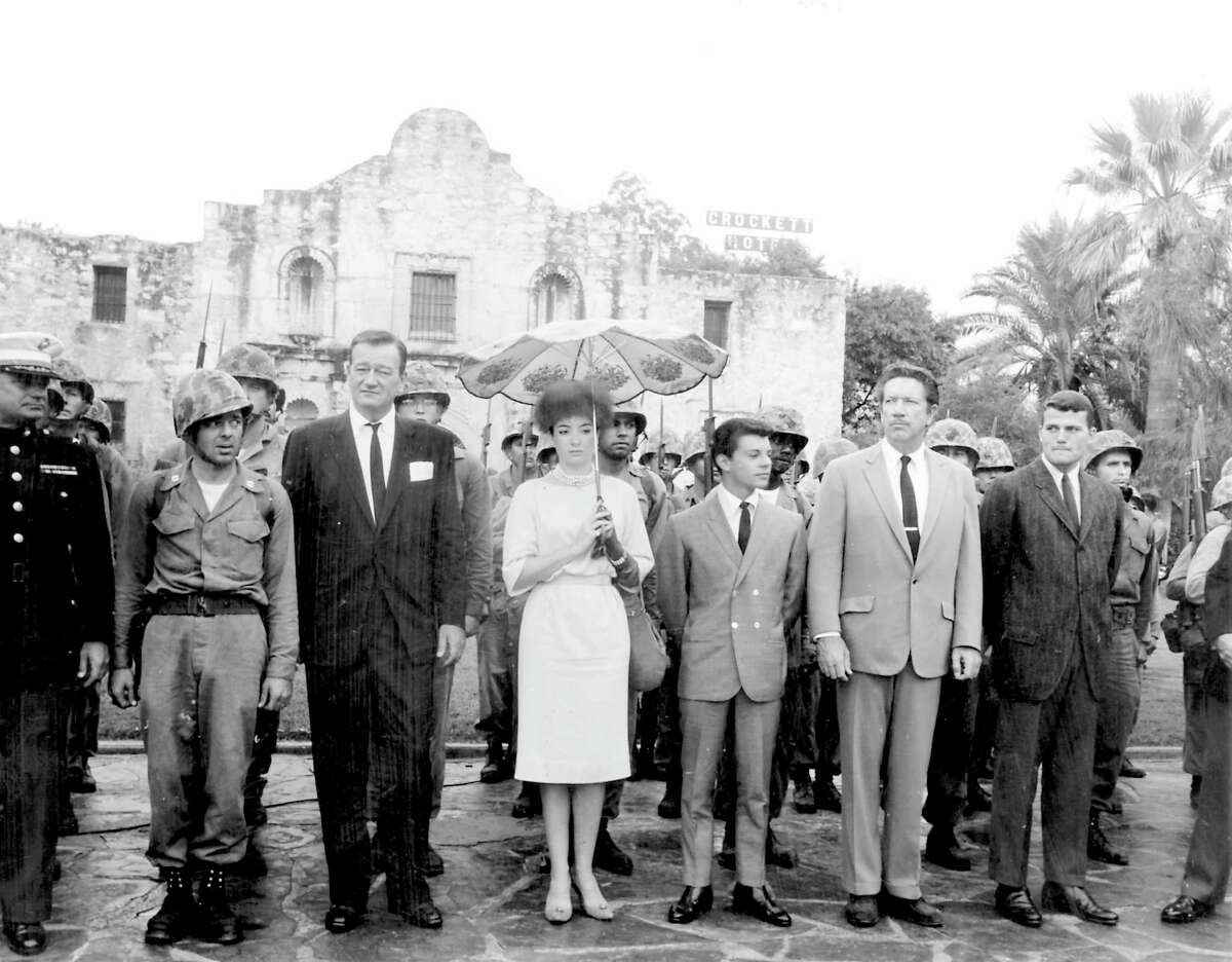 """Cast members of the 1960 film """"The Alamo,"""" including (from left of the helmeted soldier) John Wayne, Linda Cristal, Frankie Avalon, Richard Boone and Pat Wayne, pay tribute to the fallen defenders of the Alamo during a ceremony on Alamo Plaza on Oct. 24, 1960, the morning of the world premiere of the film."""