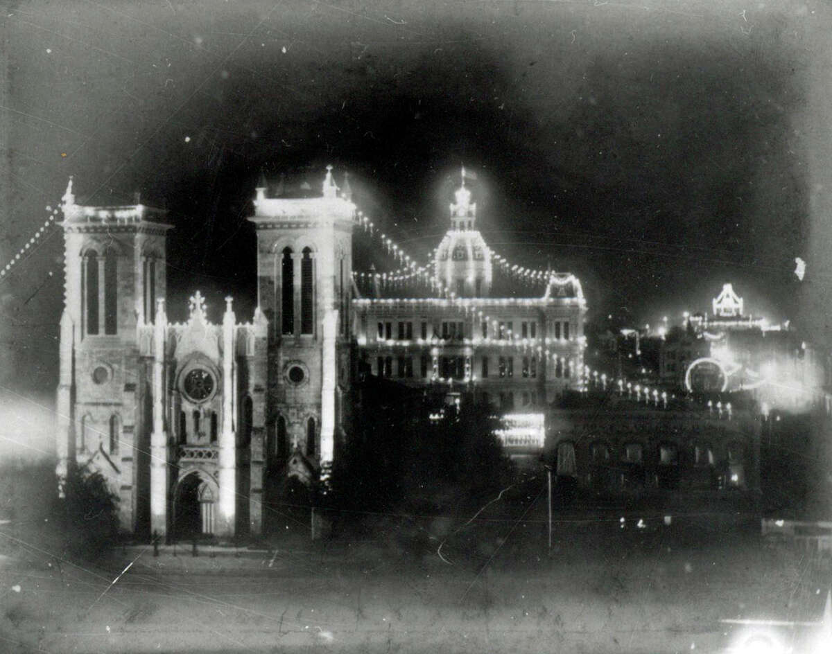 Carnival Illuminations on San Fernando Cathedral, circa 1904. Photograph shows nighttime view, from building on east side of Main Plaza, looking west toward San Fernando Cathedral, decorated with lights for Spring Carnival (later Fiesta San Antonio). In background are City Hall and City Market (in distance on far right), also decorated with lights.