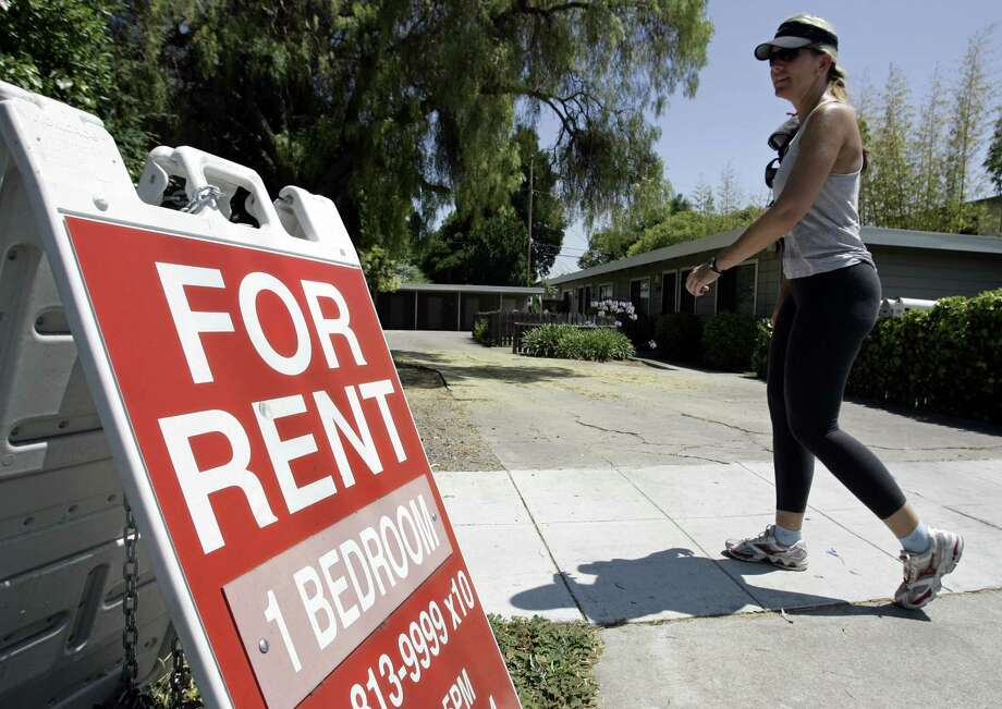 """FILE - In this July 19, 2006 file photo, a woman walks next to a """"For Rent"""" sign at an apartment complex in Palo Alto, Calif. Houston rental rates had the slowest annual growth in the U.S. last month. NEXT: See what $2,000 a month in rent will get you in Houston. Photo: PAUL SAKUMA, AP / AP"""