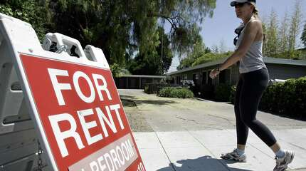 """FILE - In this July 19, 2006 file photo, a woman walks next to a """"For Rent"""" sign at an apartment complex in Palo Alto, Calif. Real estate data firm Zillow reports on U.S. home rental prices in December 2014 on Friday, Jan. 23, 2015."""