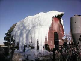 In this Jan. 17, 2015, photo, ice covers Bruce and Carol Anderbery's barn in rural Axtell, Neb. The Anderbery's wanted to make room for a new building on their farm by demolishing the old barn. According to the Daily Citizen, Bruce decided in December that pouring massive amounts of water on the barn was the easiest way to bring it down.
