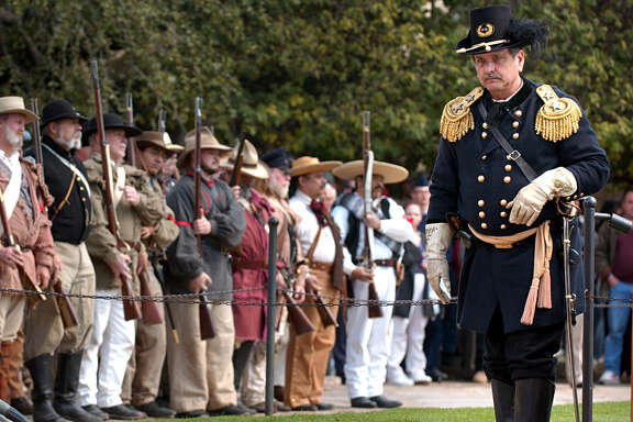 Union Major General David Twiggs (right), portrayed by Wayne Vick, surrenders to the Alamo Rifles of Texas State Troops durring the reinactment in front of the Alamo, Saturday, Feb. 14, 2004.