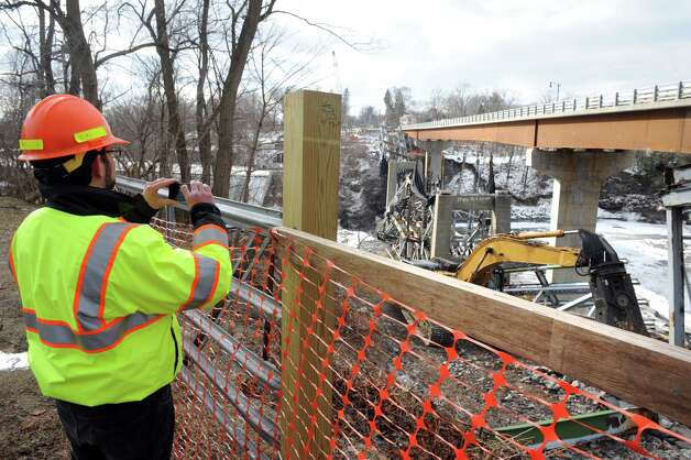 Bryan Viggiani with the New York State Department of Transportation take a photograph of the old route 40 bridge over the Hoosick River that was demolished on Friday Jan. 23, 2015 in Schaghticoke, N.Y. The old bridge built in 1942 was replaced by the new bridge which opened on Nov. 14, 2014.(Michael P. Farrell/Times Union) Photo: Michael P. Farrell