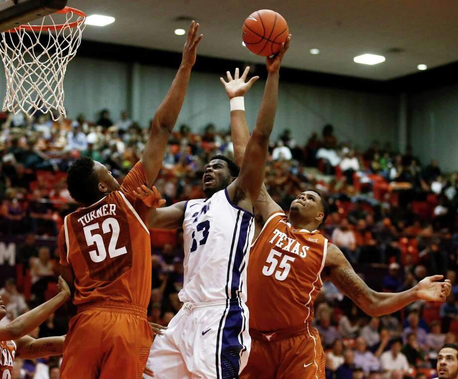 TCU forward Chris Washburn shoots inside the lane against Texas forward Myles Turner (left) and center Cameron Ridley (right) during the second half on Jan. 19, 2015, in Fort Worth. Texas won 66-48. Photo: Jim Cowsert /Associated Press / FR170531 AP