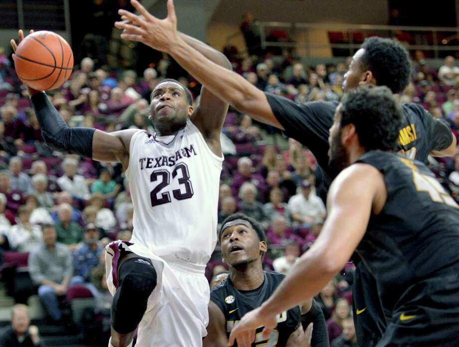Texas A&M's Danuel House drives the lane against Missouri defenders for a basket. Photo: Sam Craft /Bryan-College Station Eagle / College Station Eagle
